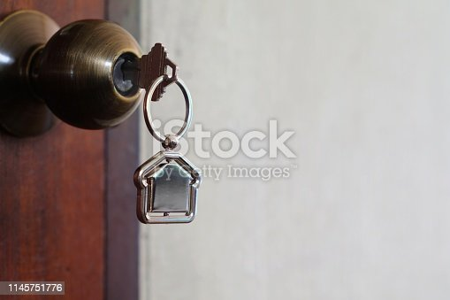 1135927471 istock photo House key with home keyring in keyhole on wood door, copy space 1145751776