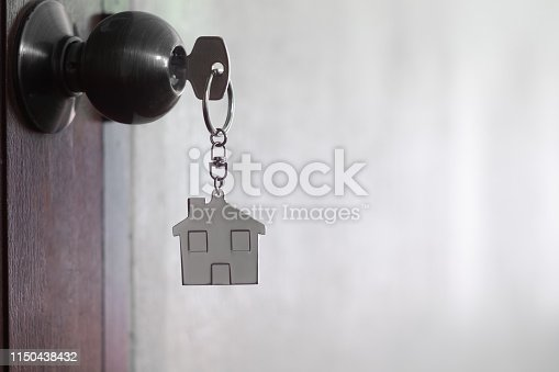 1135927471 istock photo House key with home keyring in keyhole on wood door, copy space 1150438432