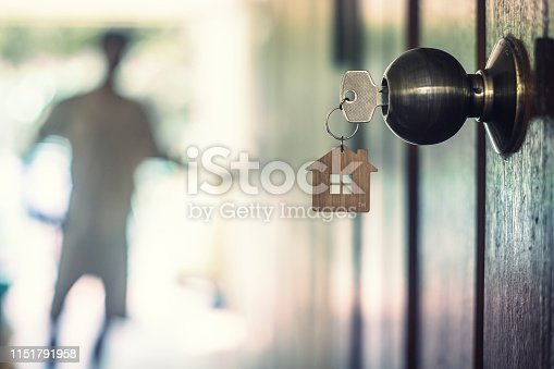 istock House key with home keyring in keyhole on wood door, copy space 1151791958