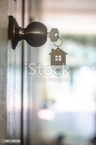 istock House key with home keyring in keyhole on wood door, copy space 1160148209