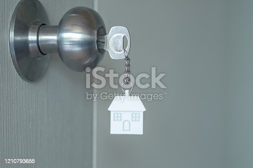 1135927471 istock photo House key with home keyring in keyhole on wood door, copy space 1210793655