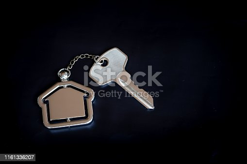 1135927471 istock photo House key with home keyring in on black background, real estate concept, copy space 1161336207