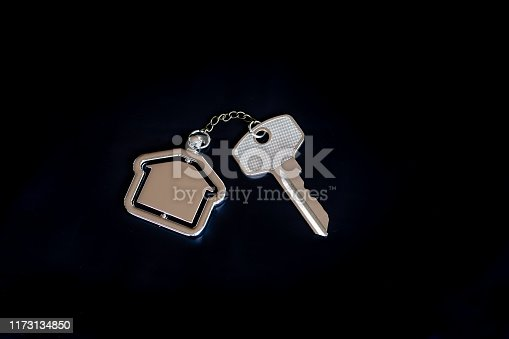 1135927471 istock photo House key with home keyring in on black background, real estate concept, copy space 1173134850