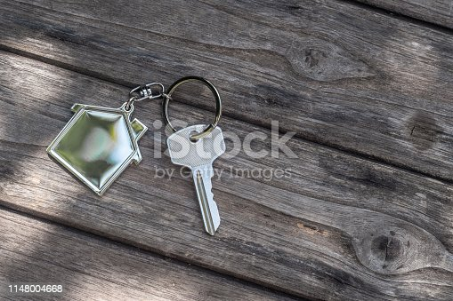 1135927471 istock photo House key with home keyring in on old wood background, copy space 1148004668