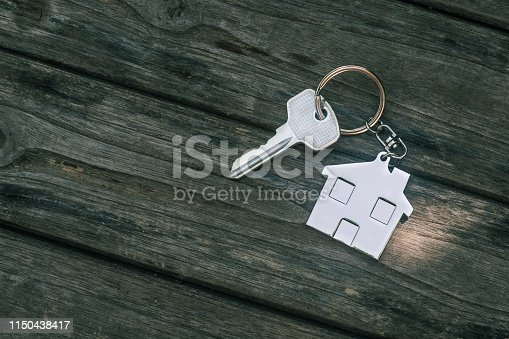 1135927471 istock photo House key with home keyring in on old wood background, copy space 1150438417