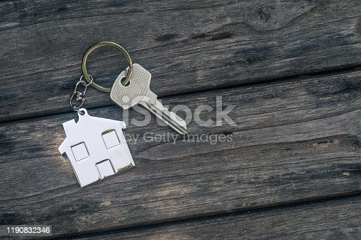 1135927471 istock photo House key with home keyring in on old wood background, copy space 1190832346