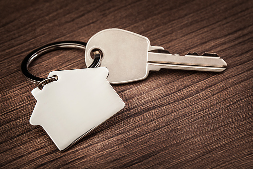 istock house key with house shaped keychain ring on vintage brown woodenn desk, concept for real estate and moving home or renting property 862736842