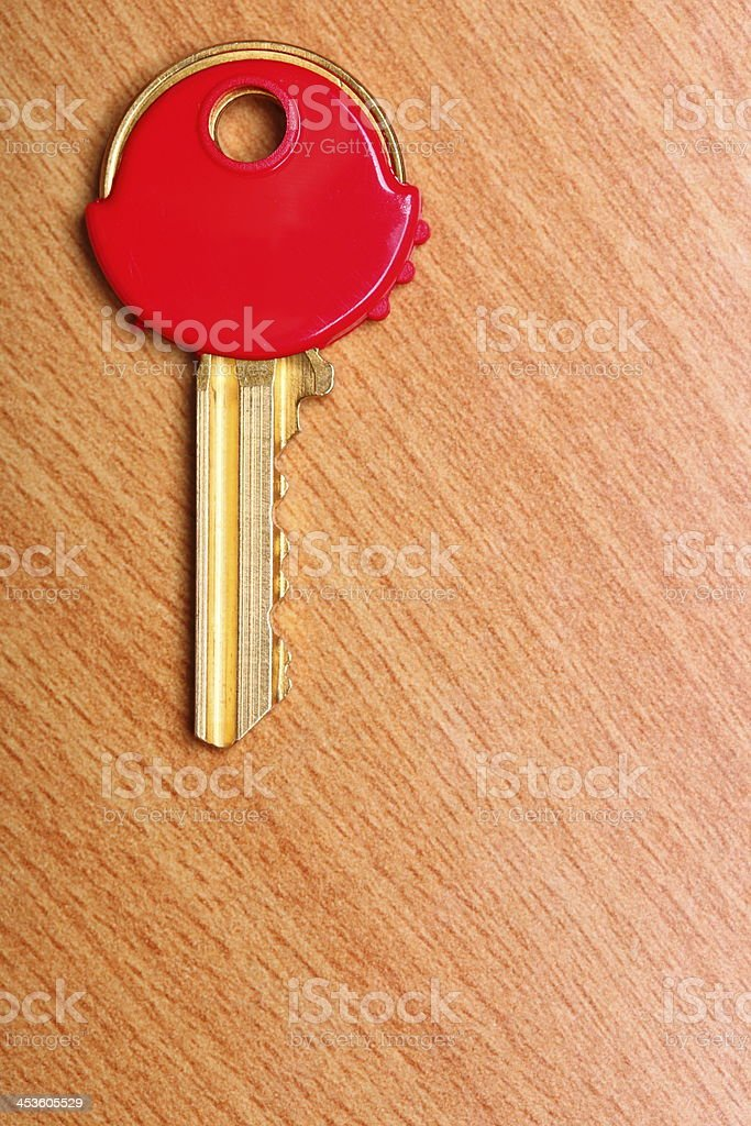 House key with red plastic coats caps on table stock photo