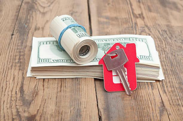 House keys over the hundred dollar banknotes stock photo