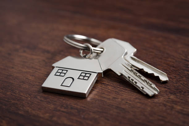 House keys Close up of house keys on a house shaped keychain on wooden background. Concept for real estate, moving home or renting property on dark wood. real estate sign stock pictures, royalty-free photos & images