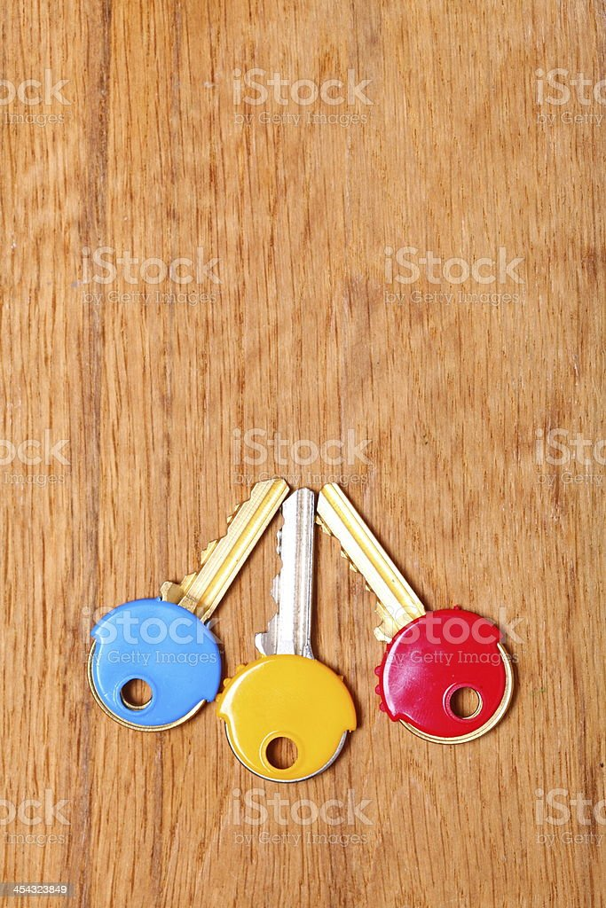 House keys with colorful plastic coats caps on table stock photo