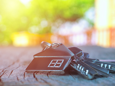 istock House keys with house figure on desk, out of focus background 1132135635