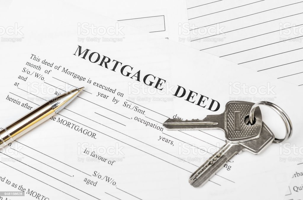 house keys with pen on mortgage deed form top view stock
