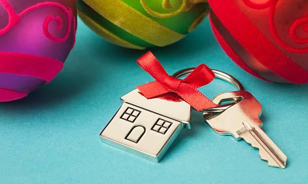 house keys with ribbon and christmas ornaments - schlüssel dekorationen stock-fotos und bilder