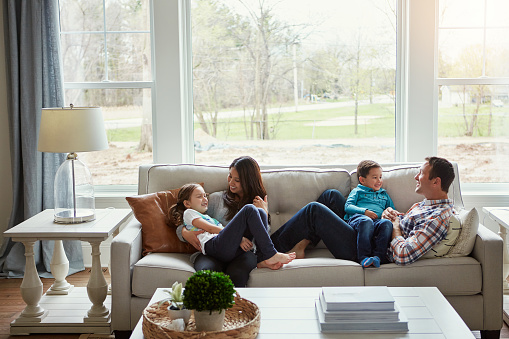 Shot of a happy young family of four relaxing together on the sofa at home