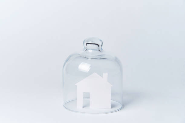 a house made of white paper under glass on a white background. - trap house stock pictures, royalty-free photos & images