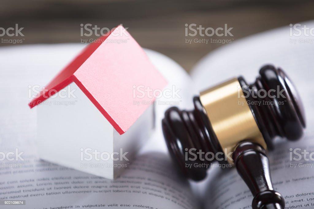 Hausmodell und Hammer auf Rechtsbuch – Foto