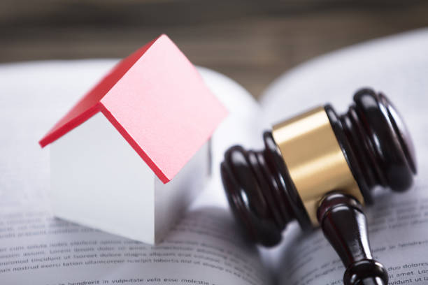 house model and gavel on law book - real estate law stock photos and pictures