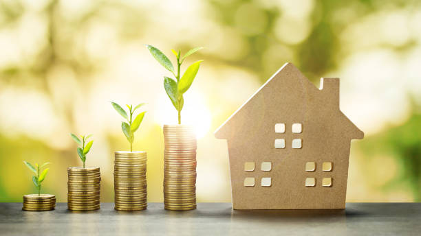 House Model and Golden Coins Stacks with blur Background.Savings Plans for Housing,Finance and Banking about House concept. stock photo