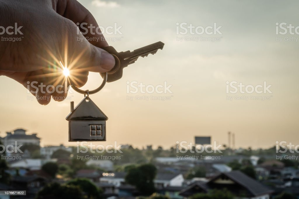 House model and key in home insurance broker agent  hand or in salesman person. Real estate agent offer house, property insurance and security, affordable housing concepts stock photo