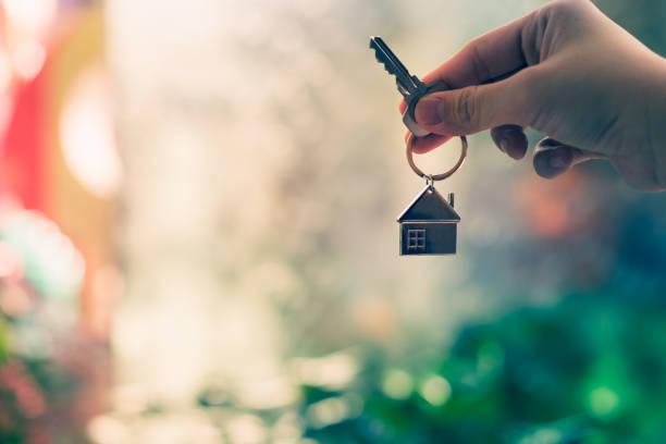 casa modelo e chave na mão do agente corretora de seguros em casa ou na pessoa do vendedor. casa de oferta de imóveis, seguros de propriedade e segurança, preços acessível habitação conceitos - chave - fotografias e filmes do acervo