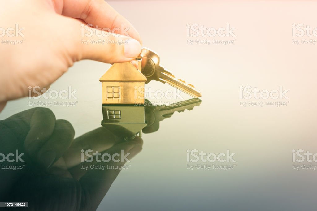 House model and key in home insurance broker agent 'u2018s hand or in salesman person. Real estate agent offer house, property insurance and security, affordable housing concepts stock photo