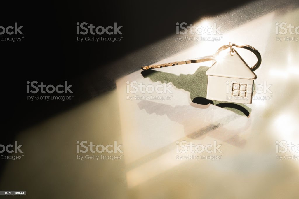House model and key in home with light from window. Real estate agent offer house, property insurance and security, affordable housing concepts stock photo