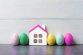House model and painted Easter eggs over white wooden background.