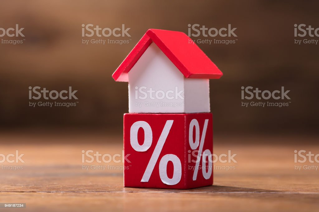 House Model And Percentage Red Block On Table stock photo