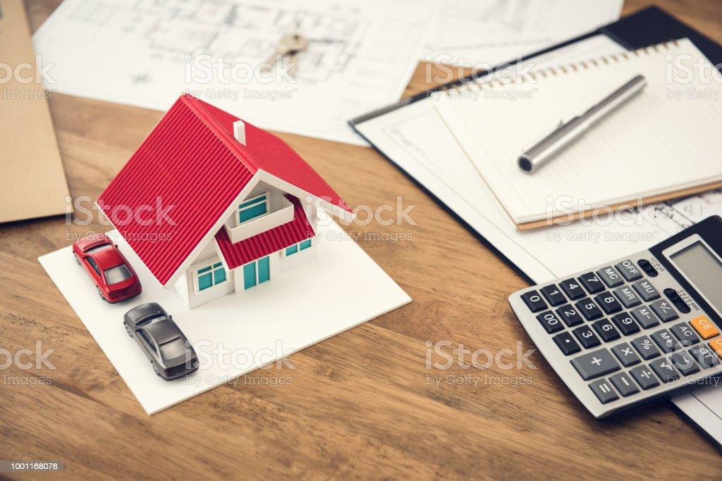 Hausmodell, Taschenrechner und Dokumente auf Holztisch – Foto