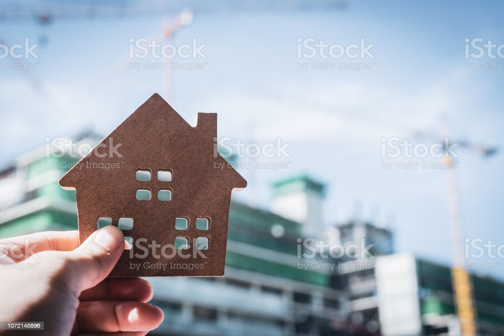House model in home insurance broker agent 'u2018s hand or in salesman person. Real estate agent offer house, property insurance and security, affordable housing concepts stock photo