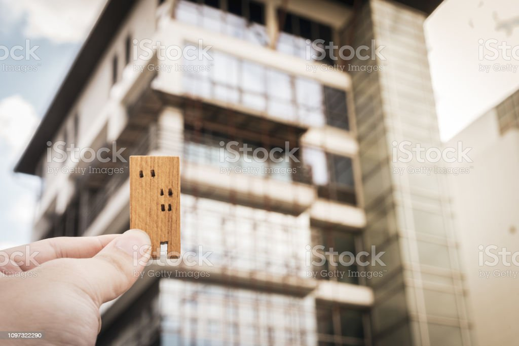House model in home insurance broker agent 'u2018s hand or in salesman person with blur building. Real estate agent offer house, property insurance and security, affordable housing concepts stock photo