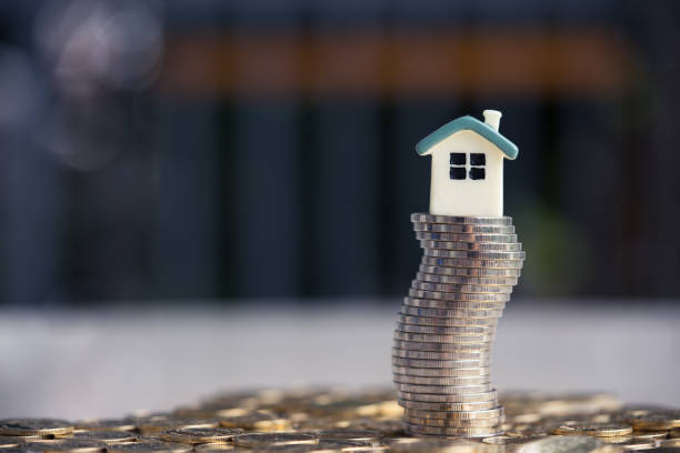 House model on coins stack. Concept for property ladder, mortgage and real estate investment . stock photo