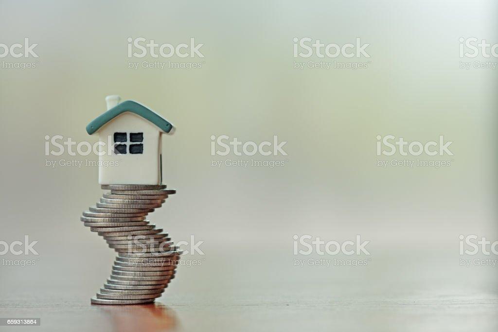 Ev modeli üzerinde sikke yığını. Konsept Emlak merdiven, ipotek ve gayrimenkul yatırım için. stok fotoğrafı
