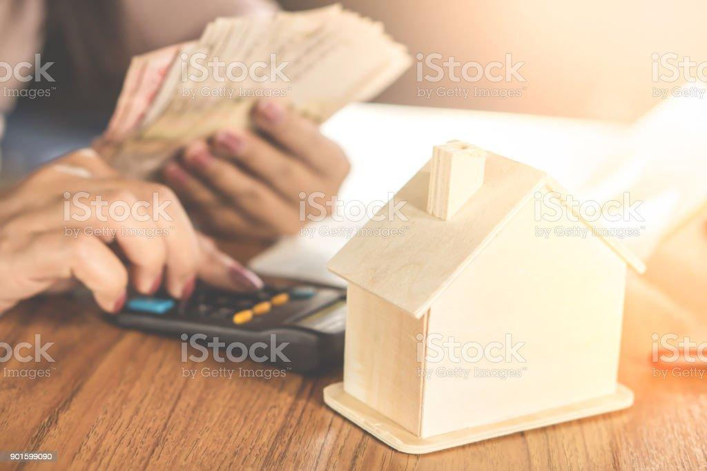 Hausmodell auf Holztisch mit Frau Hand Geldzählen im Hintergrund – Foto