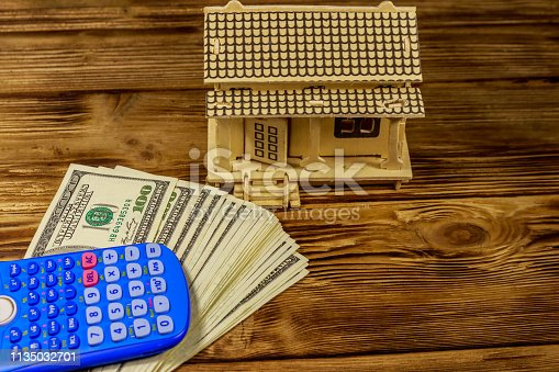 House model, U.S. one hundred dollar bills and calculator on wooden background. Property investment, home loan, house mortgage, real estate concept