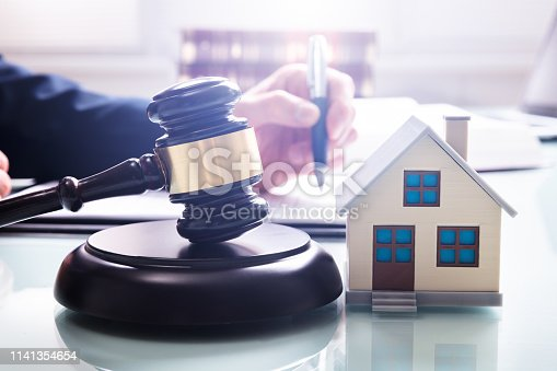 istock House Model With Gavel In Front Of A Businessperson 1141354654