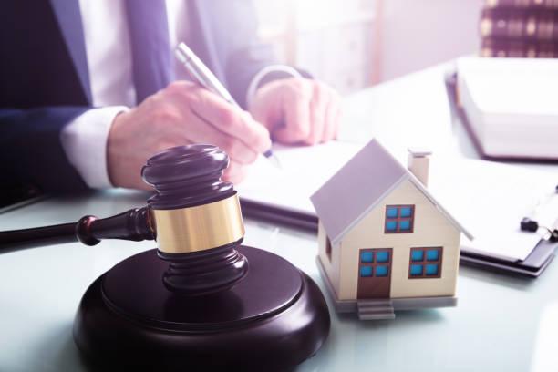 modelo de la casa con gavel frente a una persona de negocios - embargo hipotecario fotografías e imágenes de stock
