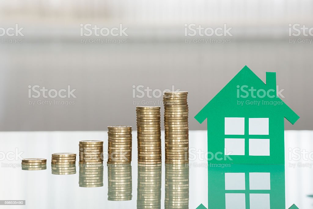 House Model With Stacked Coins On Desk photo libre de droits