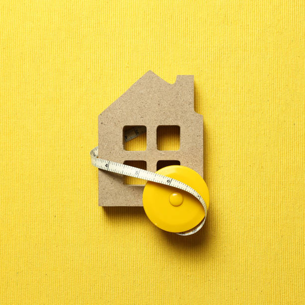 House model with tape measure on yellow fabric background. Buying a house, house size, real estate concept stock photo
