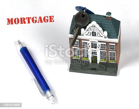 House model with key and pen on mortgage deal ready for signing