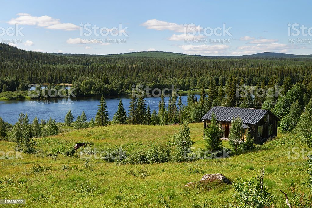 House near lake in the middle of taiga forest royalty-free stock photo
