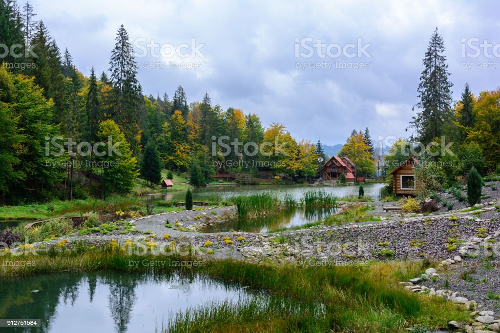 House near the lake in the forest, autumn day.  Leaf fall landscape. stock photo