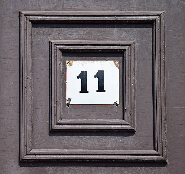 House number 11 on the wooden door of a building stock photo