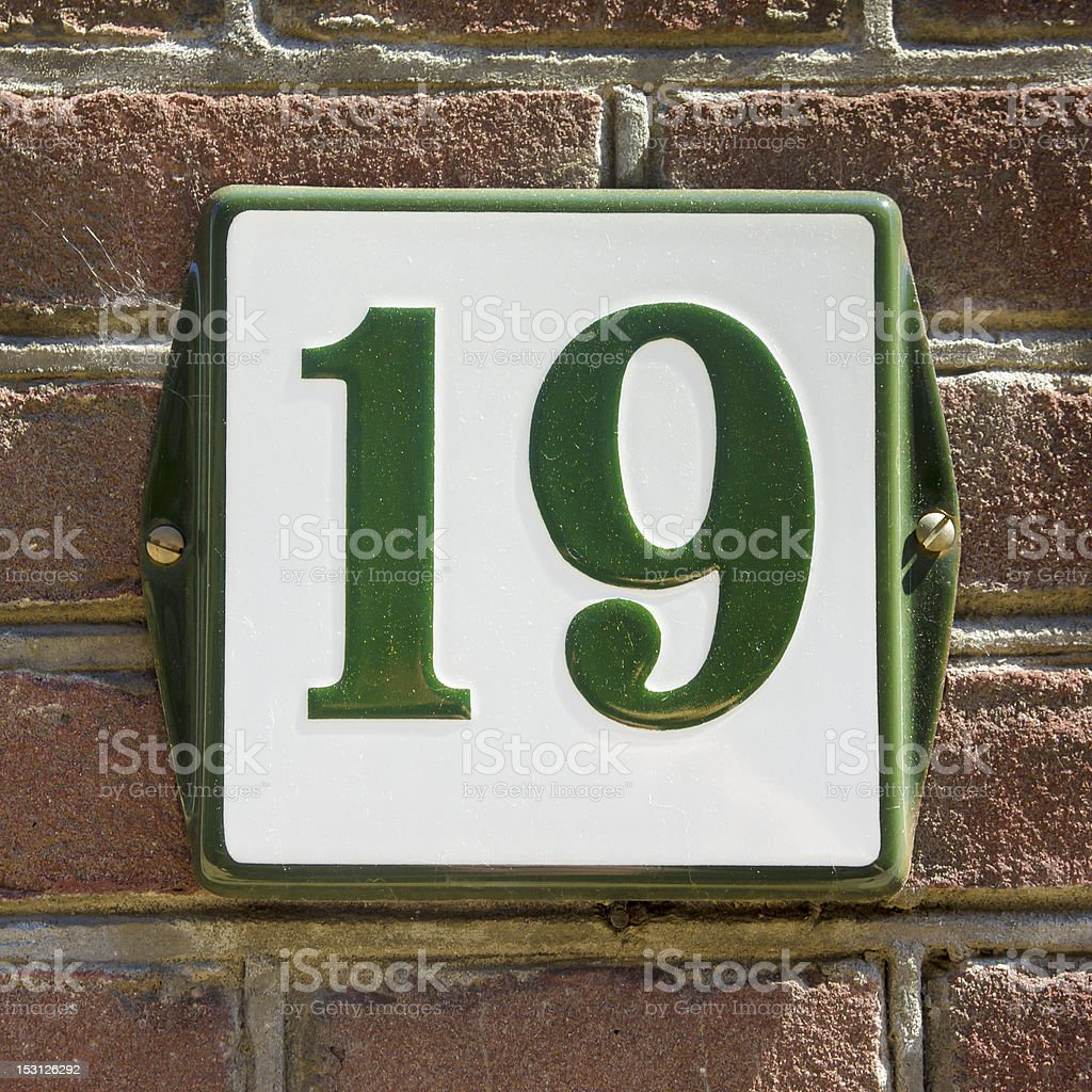 enameled house number nineteen. Green lettering on a white background