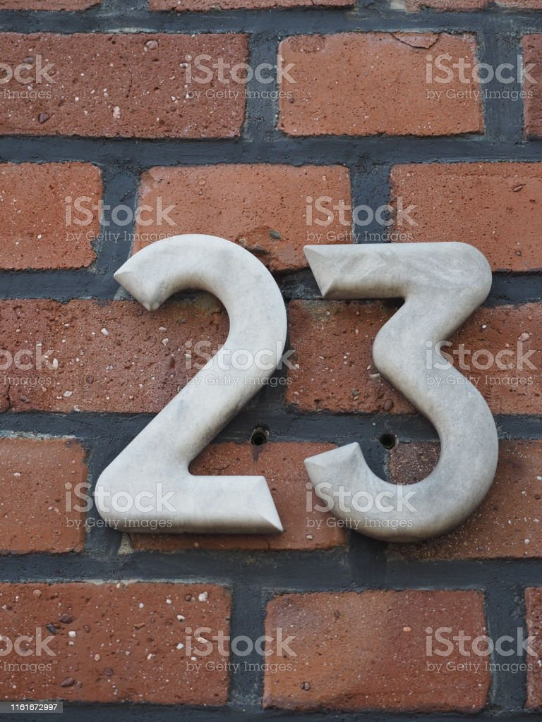 House number 23, white numbers on a clinker wall