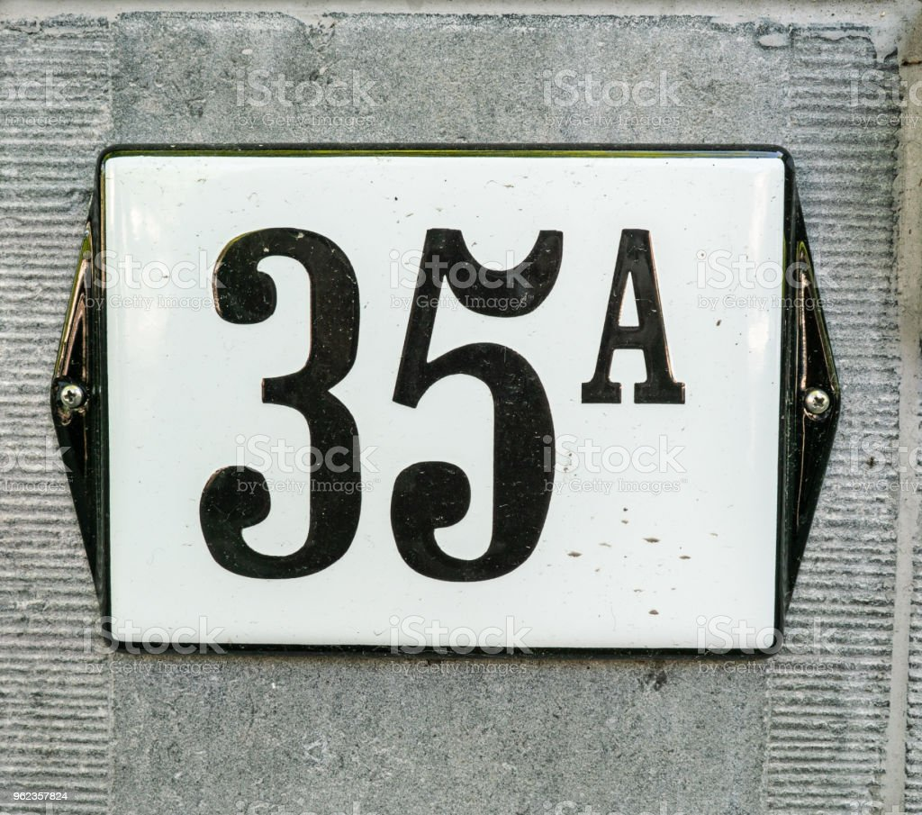 House Number 35A thirty five A, black numbers on a white plate with black border constructed to a old marmer wall stock photo