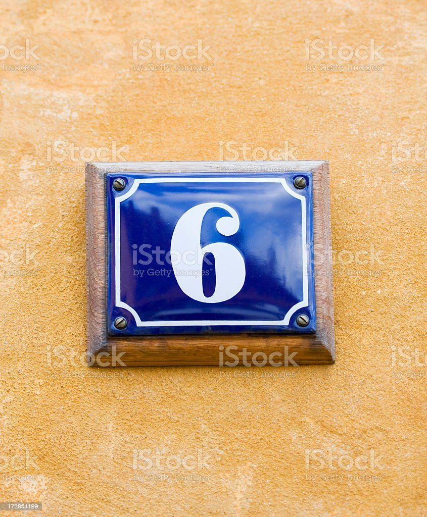 House number 6, six. Blue enamel sign on yellow wall.