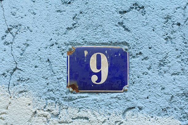 House number nine on an old blue enamel sign stock photo
