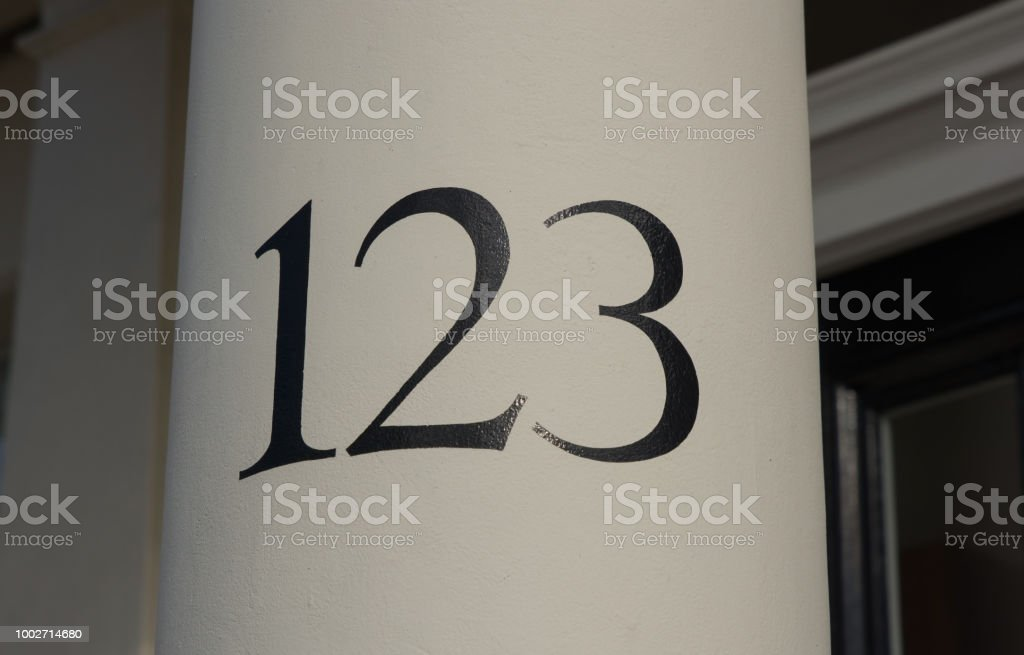 House number painted with black on white column by doorway in London,...